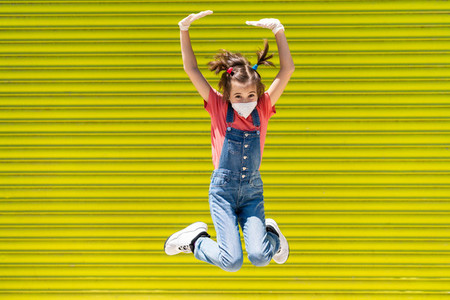 Child girl jumping wearing a protection mask against coronavirus