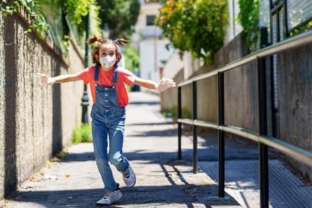 Child girl running outdoors wearing a protection mask against coronavirus during Covid 19 pandemic