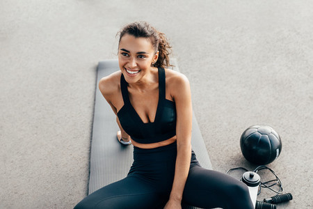 Happy fit woman sitting on a mat