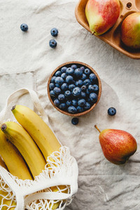 Bananas in a net bag pears and blueberry on a linen napkin Eco friendly and summer food background