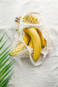Bananas in a net produce bag on a linen napkin decorated with palm leaf Eco friendly and summer concept