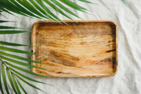 Wooden tray is made from mango tree on a linen cloth decorated palm leaf  Eco friendly and summer mock up