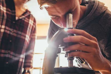 High school student using a microscope in a science class