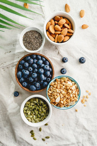Top view of breakfast ingredients like cereal  almond  blueberry  pepitas and chia seeds on a linen cloth decorated with palm leaf