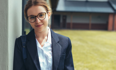 Female high school student in uniform looking at camera