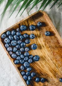 Fresh blueberry in a wooden tray on a linen light cloth Healthy eating and Summer concept