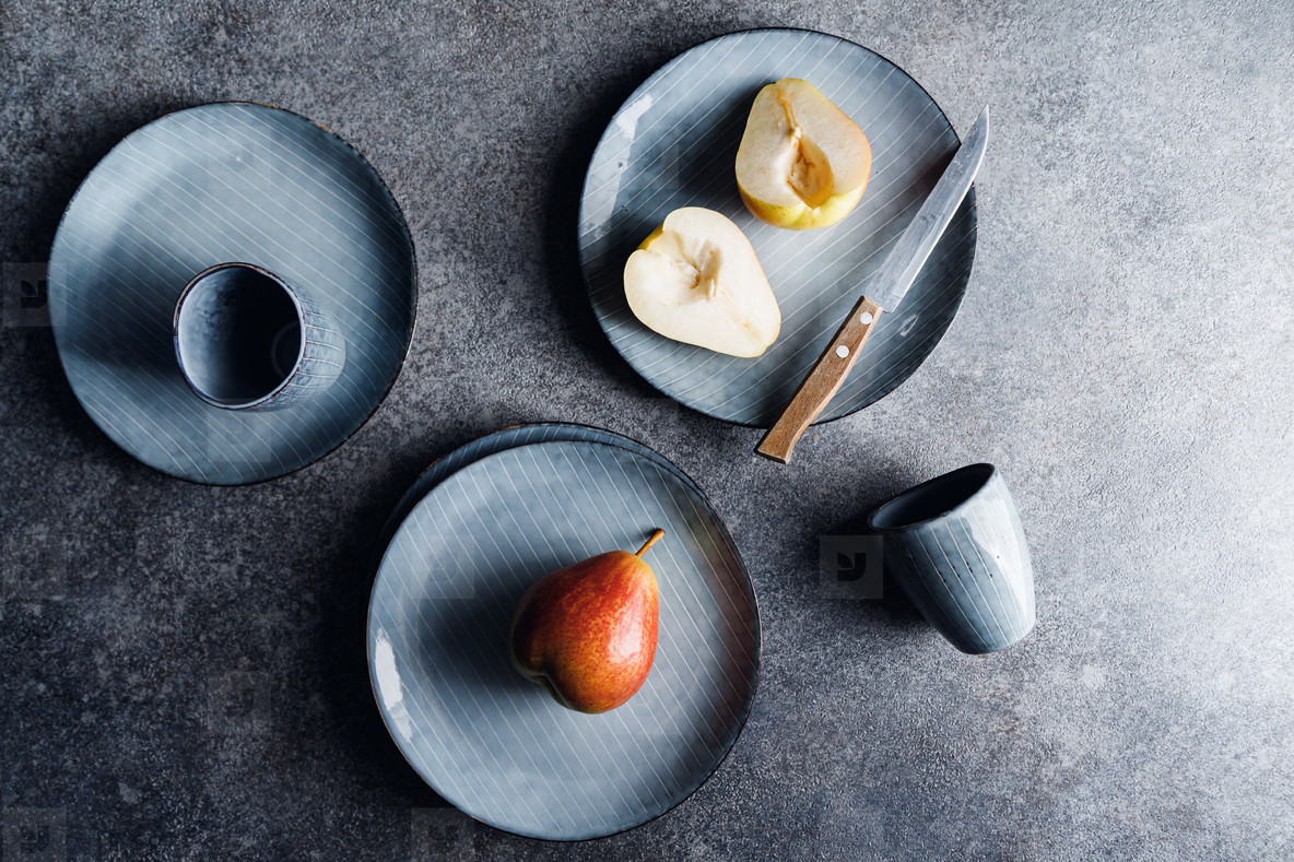 Blue food ceramic set with plates and pears over grey textured background  Minimalist style  top view