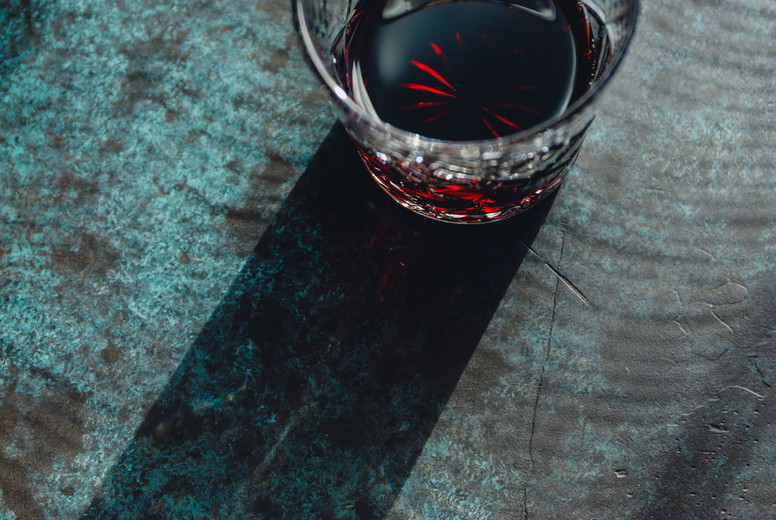 Creative image of red cocktail on a dark blue background under sunlight with contrast shadows