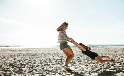 Mother spinning daughter around on the beach