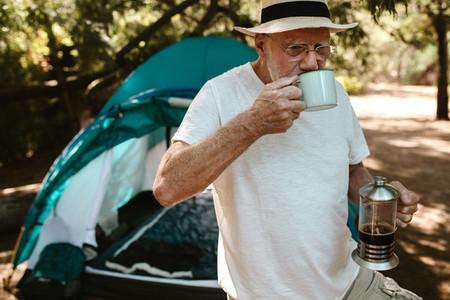 Senior man having coffee at campsite
