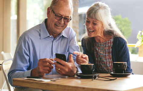Senior couple using mobile phone at a cafe