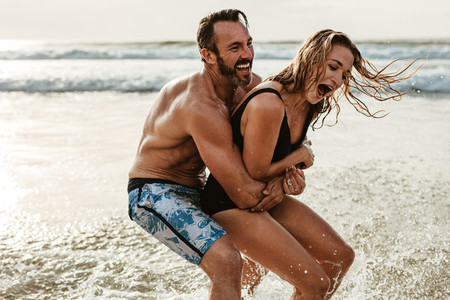 Playful couple having fun on their summer beach vacation