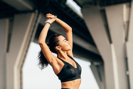 Happy athlete stretching her arm
