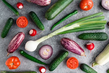 Colorful summer pattern with different fresh vegetables on a grey background  Flat lay  top view