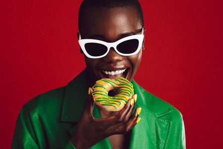 Fashionable woman eating donut