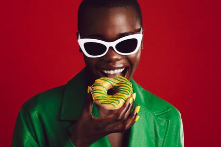 Fashionable woman eating donut