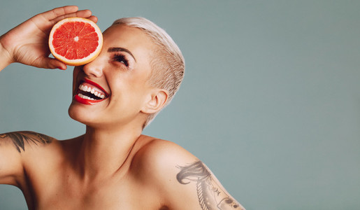 Attractive woman holding a grapefruit and smiling