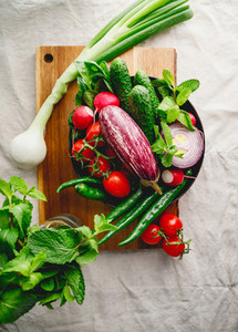 Different fresh vibrant vegetables in a plate on a wooden tray  Flat lay  top view
