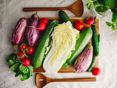 Top view of different fresh colorful vegetables on a wooden tray