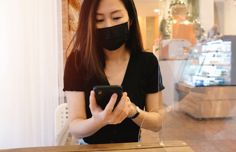 Young asian woman sitting separated in restaurant or cafe and us