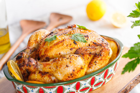 Whole roasted chicken with fresh parsley and lemon wedges in a festive dish