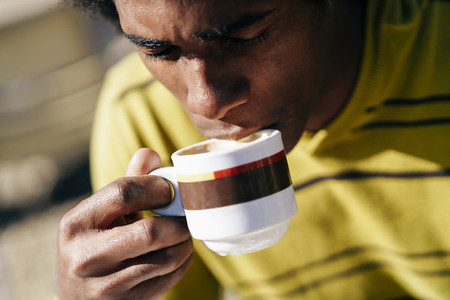 Black man enjoying coffee in cafe while sitting at the table outdoors