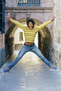 Black man with afro hair jumping for joy