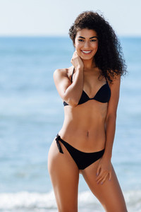 Young arabic woman with beautiful body in swimwear smiling on a tropical beach