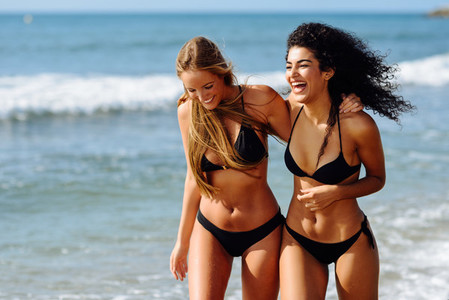 Two young women with beautiful bodies in swimwear on a tropical beach