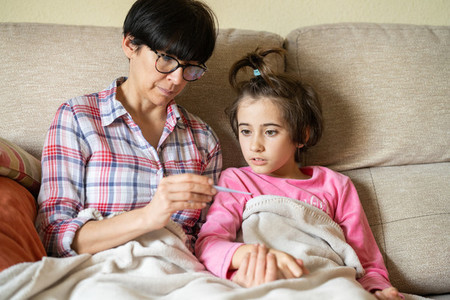 Mother measuring her daughters temperature to check for fever