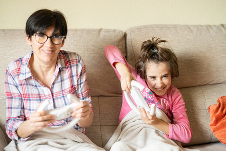 Mother and daughter playing video games at home
