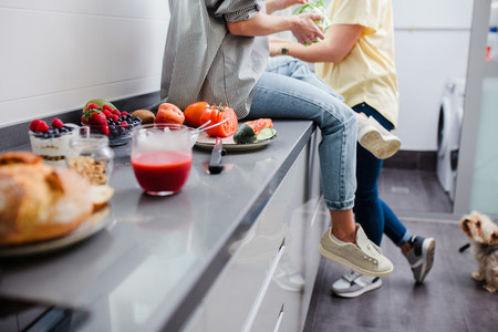 Simple healthy food concept  Cheerful friends cooking vegetable summer salad in the home kitchen