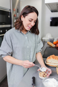 Cheerful woman cooking healty food in the home kitchen