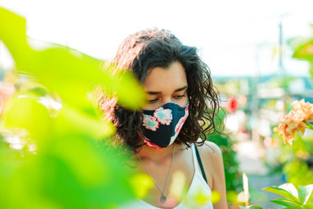 Woman with face mask gardening in greenhouse covid 19