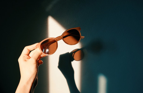 Woman hand holding fashionable sunglasses with shade of sunlight