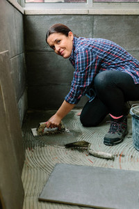 Female mason laying a new tile floor