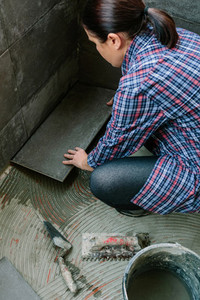 Female builder laying a new tile floor