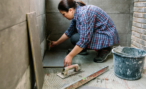 Female manual worker laying a new tile floor
