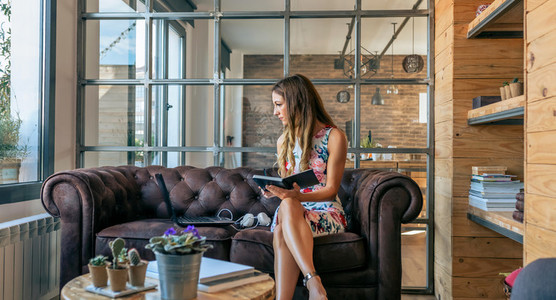 Businesswoman working with laptop sitting on the sofa