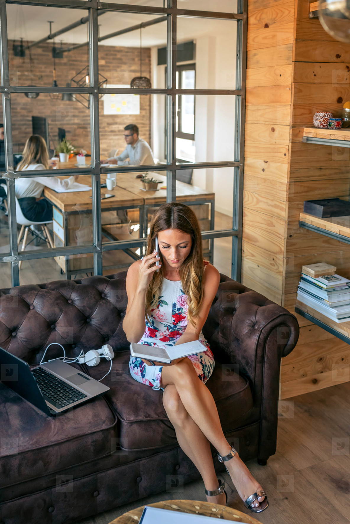 Businesswoman working with laptop talking on the phone sitting on the sofa