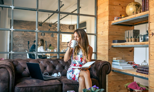 Businesswoman drinking coffee and working in a coworking office