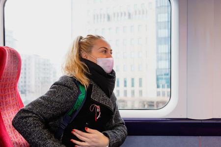 Woman with hygiene face mask keeps safety distance in the seats of a train because of the coronavirus