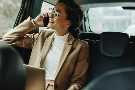 Businesswoman using phone while traveling by a car