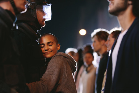Woman activist hugging a policeman