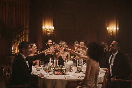 Socialites celebrating with wine at dinner party