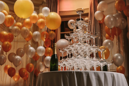 Pyramid of champagne glasses at party
