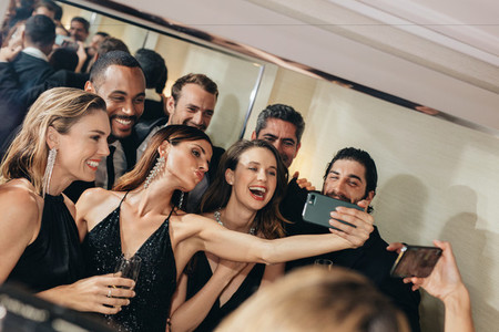 Attractive woman with friends taking selfie at a gala event