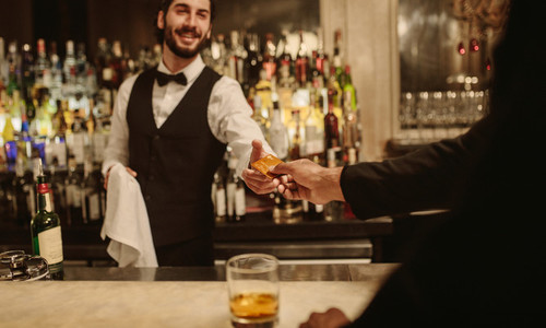 Barman accepting cashless payment
