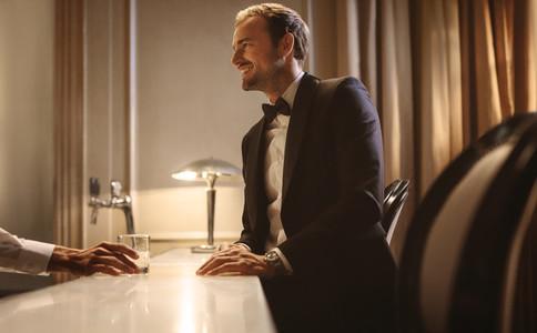 Man talking with a barman at a night club