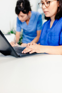 Female doctor and nurse using the laptop in the clinic